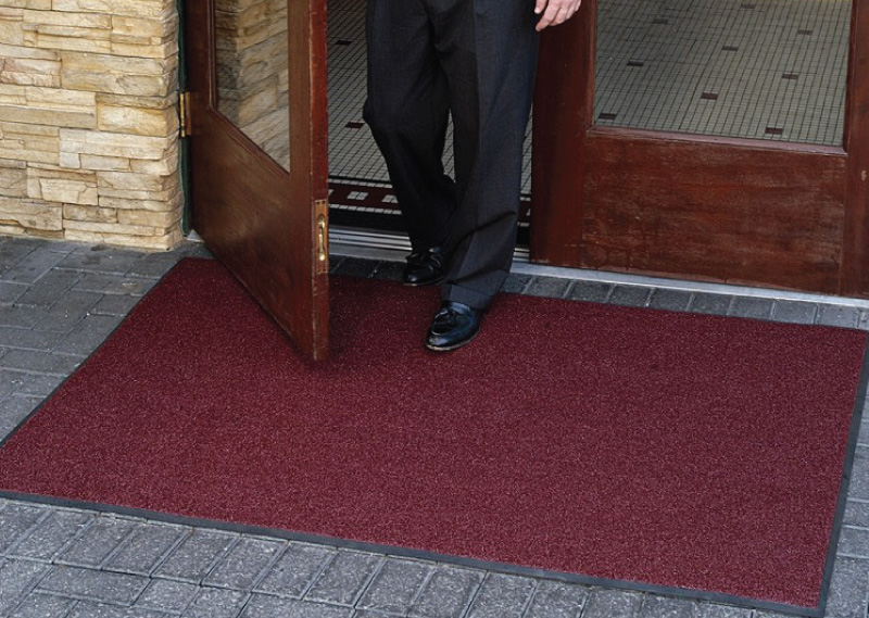 Man walking out door onto entrance mat
