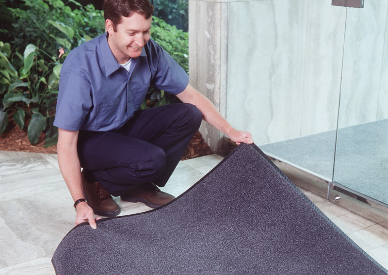 Man placing entrance mat on floor